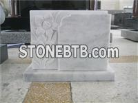White marble headstone monument with carving