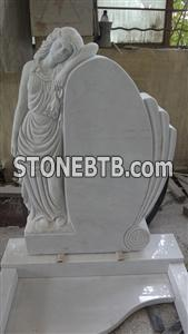 White marble headstone with angel sculpture